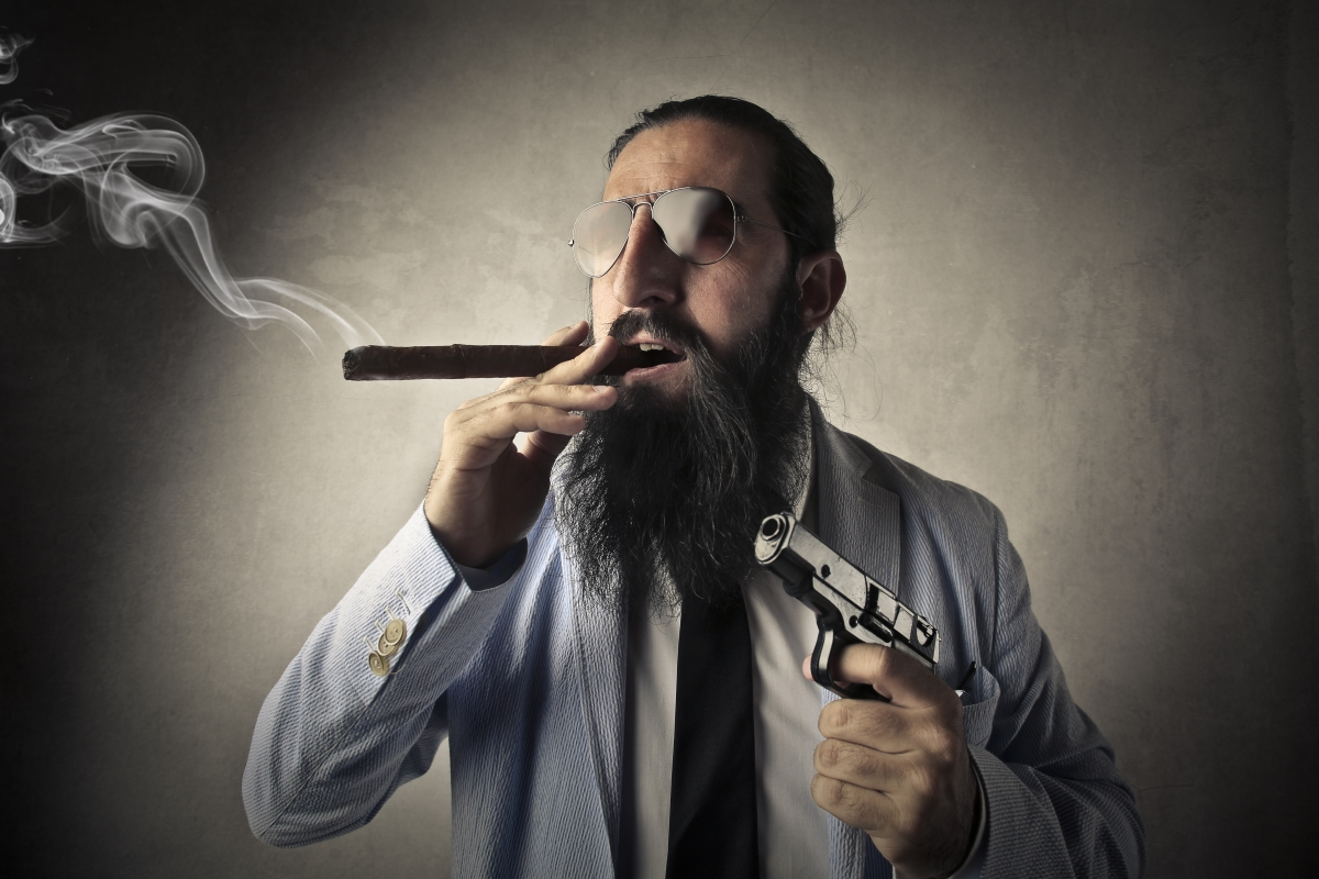 This cigar smoking, bearded gun man is being authentic